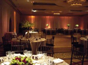 Park Hyatt ballroom with billowy fabric walls, washed with a soft amber up lights around the room and the pinspots highlighting the centerpieces